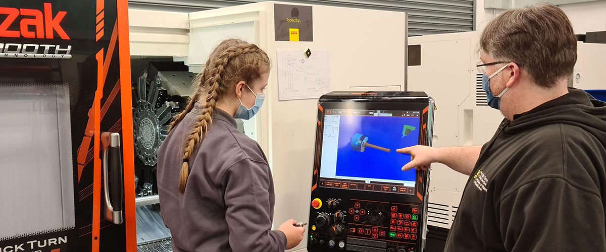 Two Students Working On Manufacturing Equipment