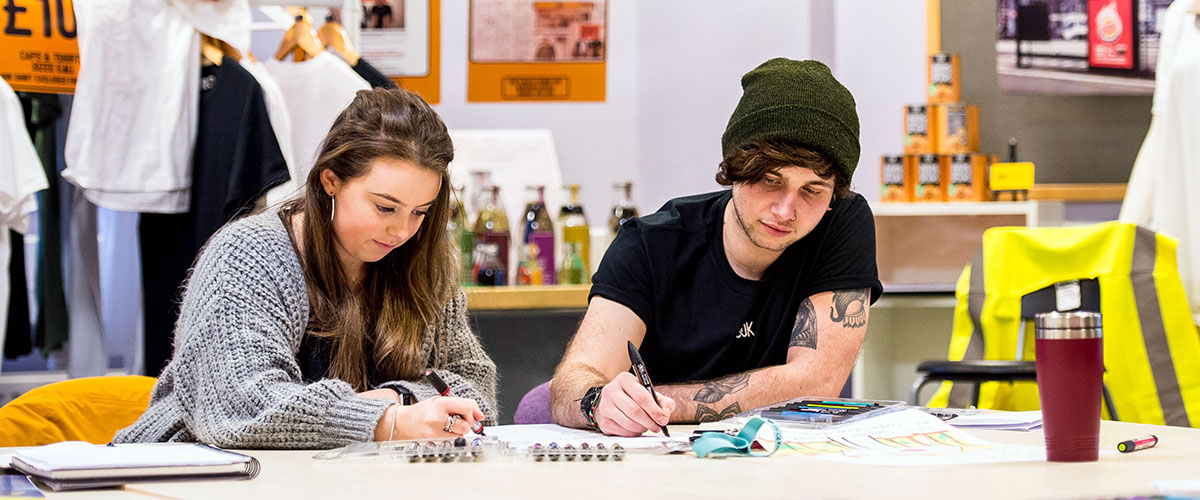 Two students writing at Swansea College of Art