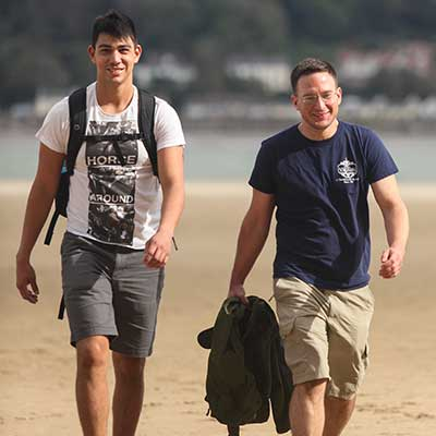 Two International Students walking on the beach